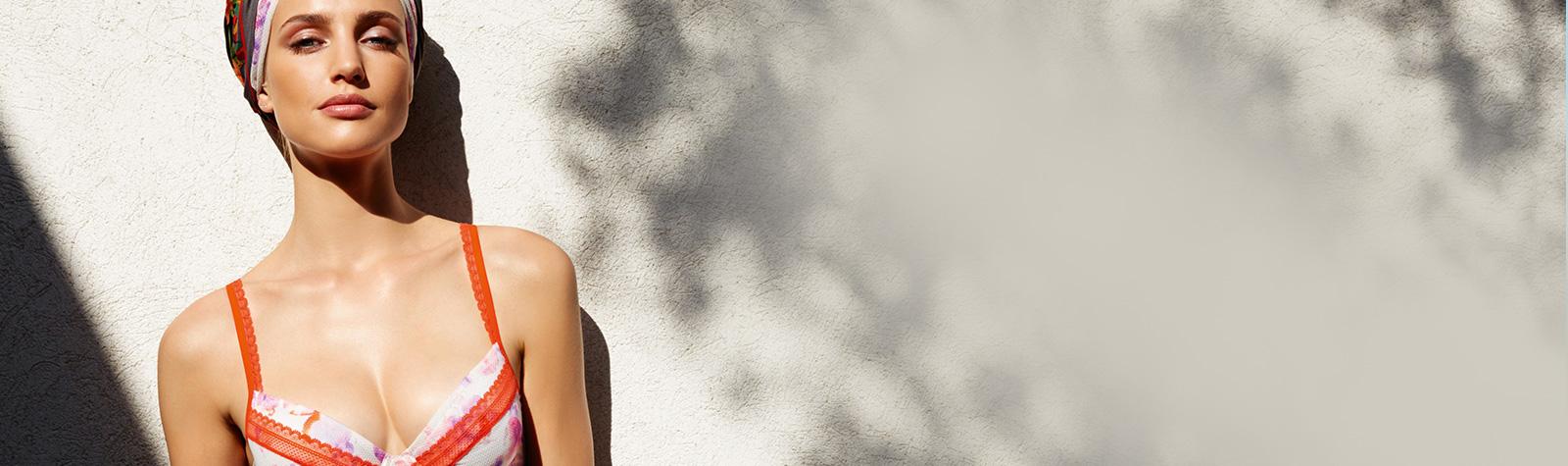 Chic Dessous Sliderbild - Frau mit Badeanzug lehnt an der Wand und schaut in die Kamera, Sommer, sonniges Ambiente